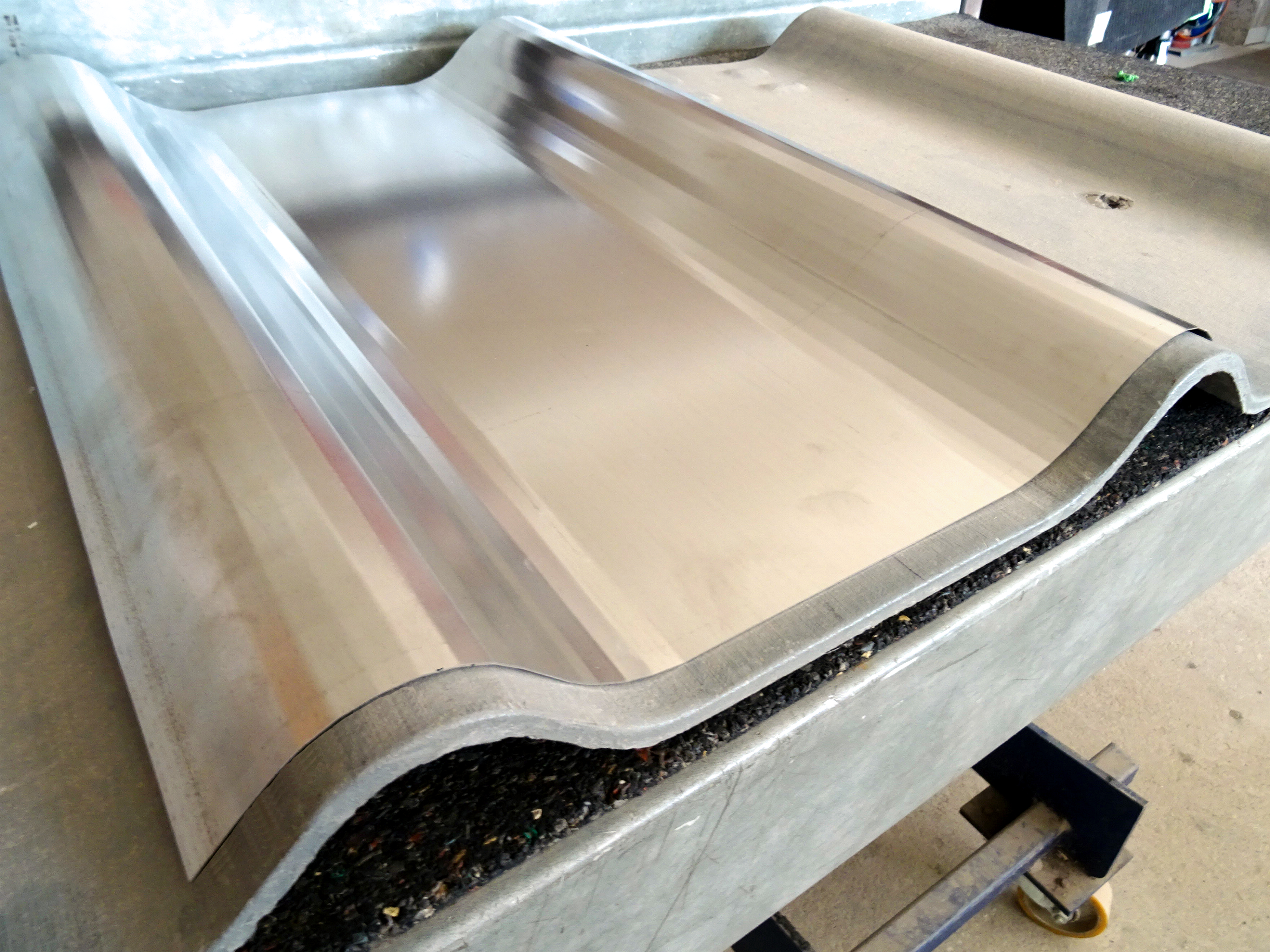Curved stainless steel panel covering a standardized roof panel